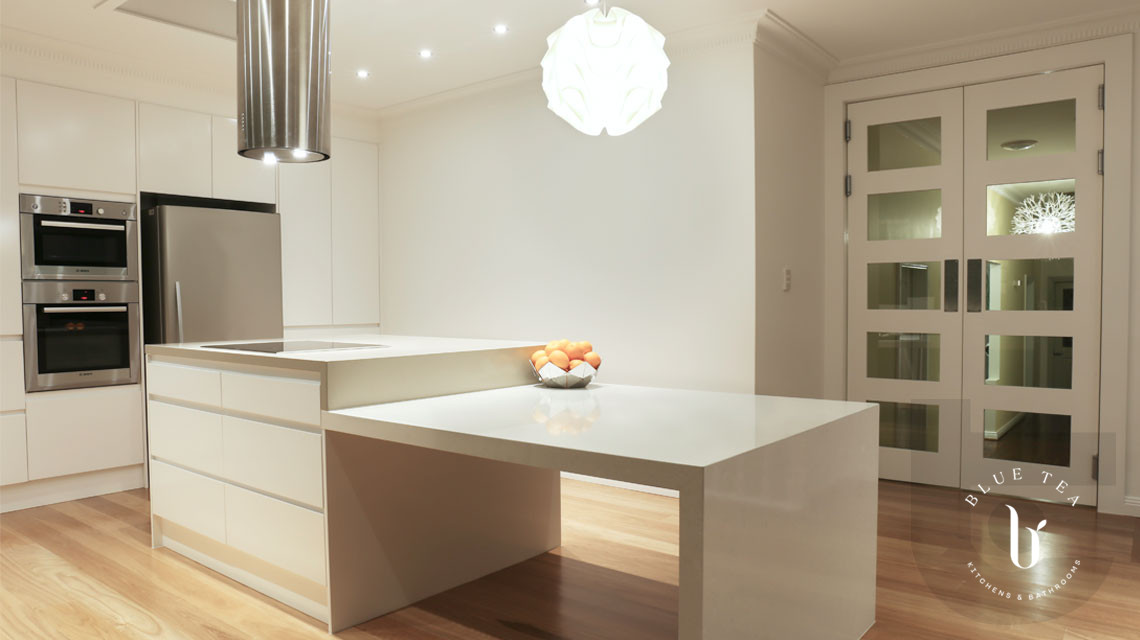 White handless kitchen with stepped island with 40mm mitred caesarstone, Croydon.