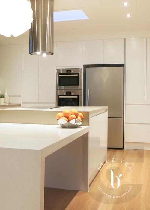 White kitchen with stepped island with 40mm mitred caesarstone, Croydon.