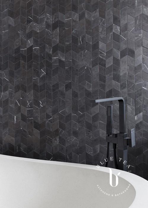 Freestanding bathtub, black tapware and feature marble tiles drummoyne.