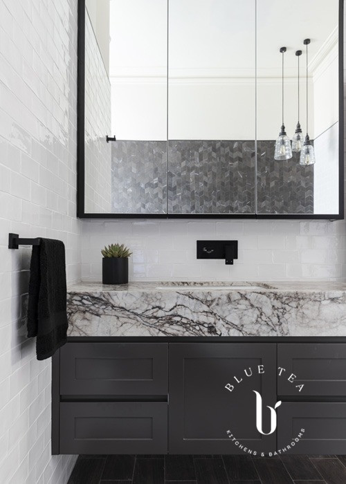 A black and white bathroom, with a thick marble benchtop in Drummoyne, Sydney by Blue Tea Kitchens