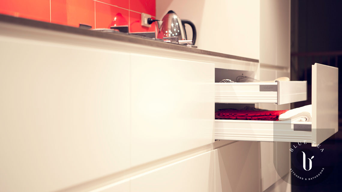 Kitchen in Maroubra with white handless drawers showing open drawer and inner drawer with an orange splashback.