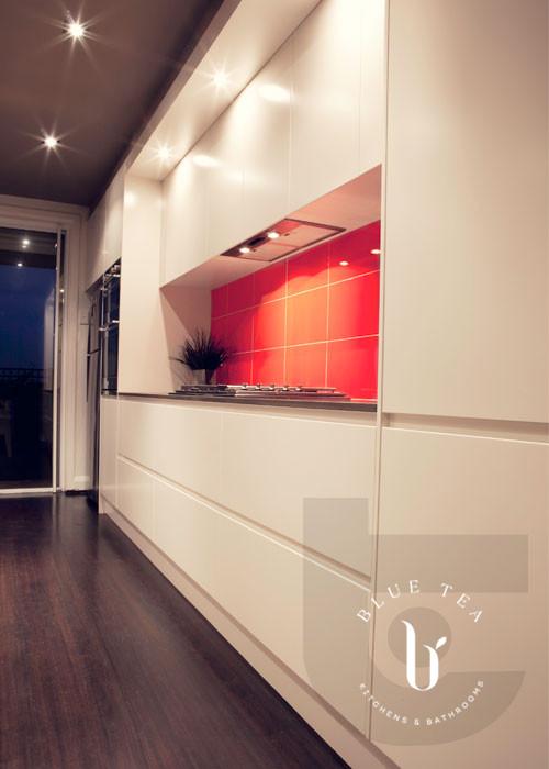 White handless polyurethane kitchen, a dark ceiling and orange tiled splashback in Maroubra, Sydney.