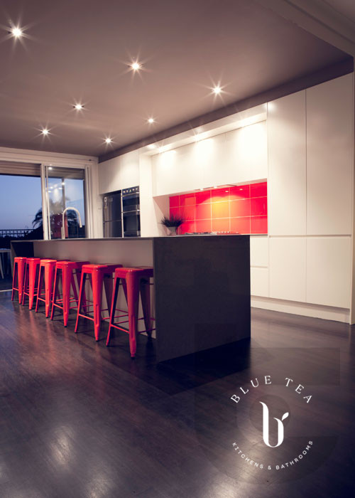 A handless white kitchen in Maroubra with an island and red stools, orange splashback and a dark feature ceiling.
