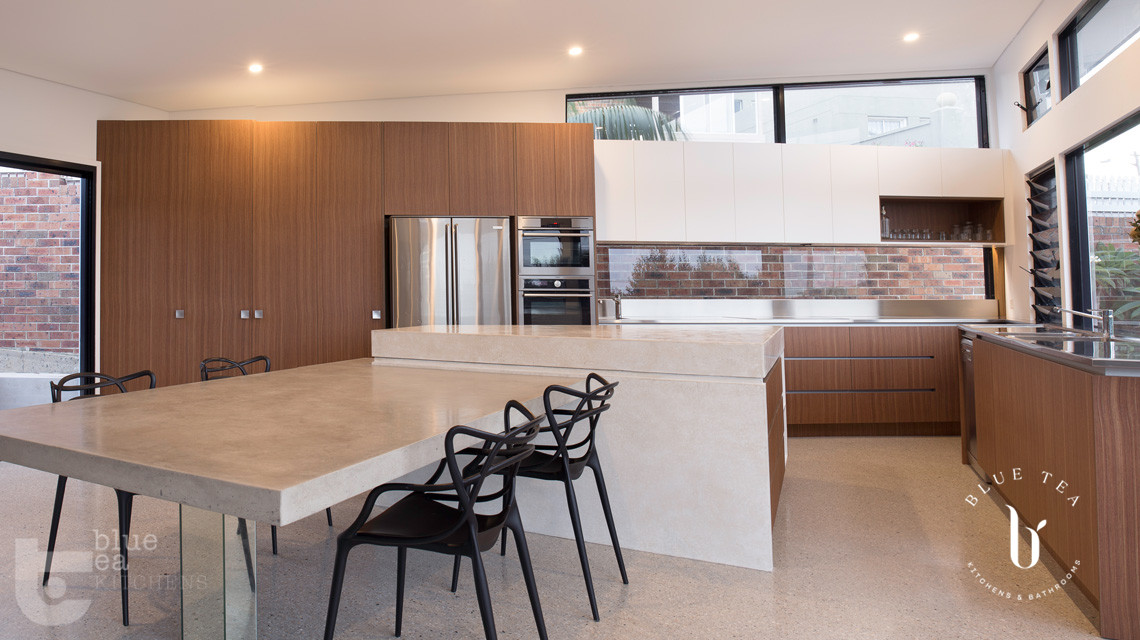 modern kitchen using concrete floors, timber veneer and polyurethane cabinets