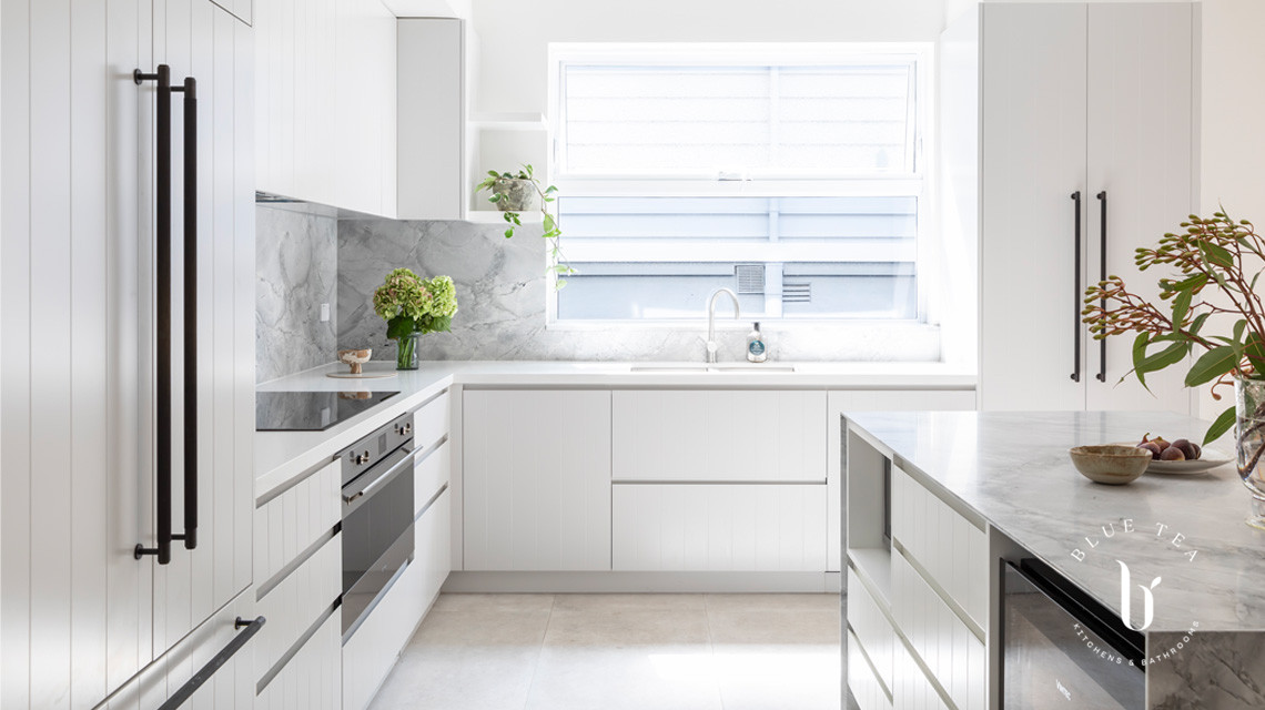 Super white dolomite marble splashback and benchtop and v-groove feature cabinetry in this Blue Tea Kitchen, Clovelly.