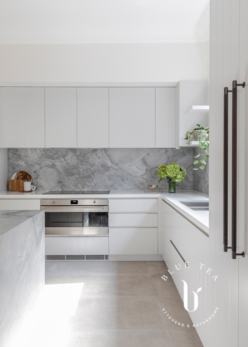 Super white dolomite marble splashback and v-groove feature cabinetry and black handles in this Blue Tea Kitchen, Clovelly.