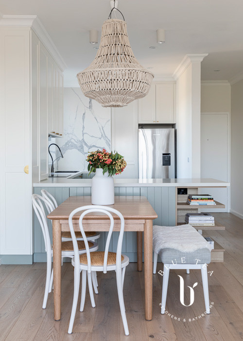North Bondi kitchen design- open plan kitchen with a dining table, a marble splashback and feature lighting