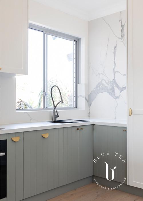 North Bondi kitchen design- V-groove doors soft blue kitchen doors, a marble splashback and brass door handles