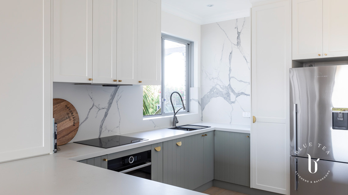Brass handles, white and soft blue shaker doors and marble splashback in our North Bondi kitchen design