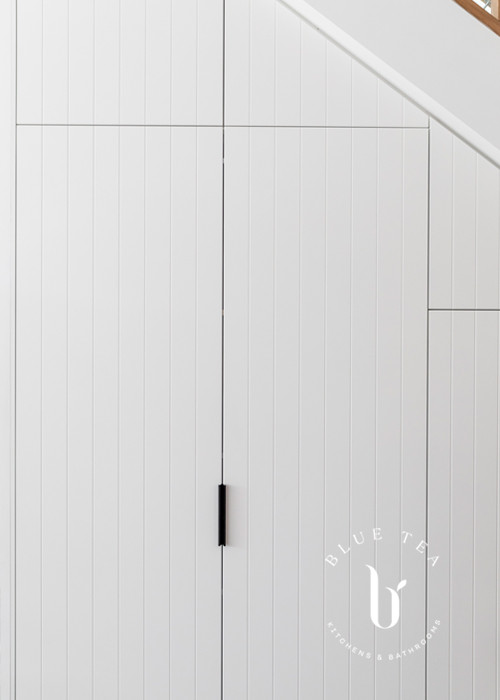 Petersham kitchen showcasing hidden laundry with white v-groove joinery details.