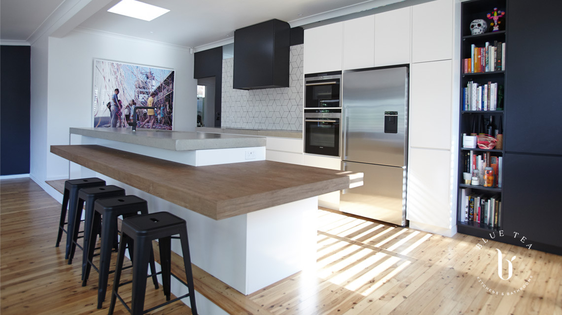 Black and white kitchen cabinetry, with a concrete and timber benchtop and tiled splashback in Waterloo, Sydney.