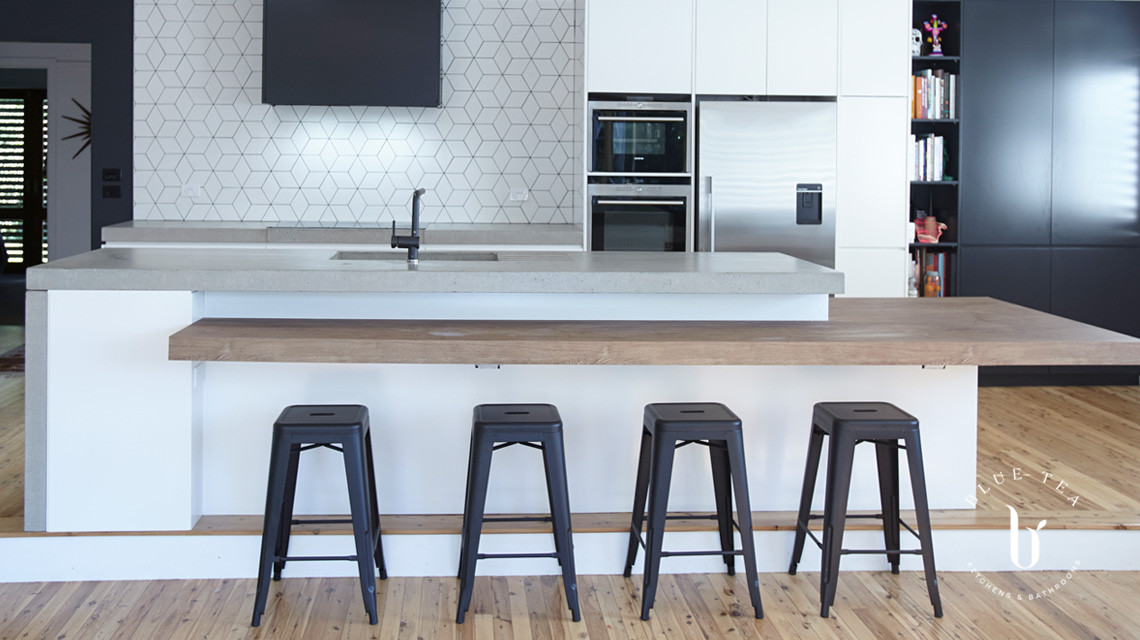Black and white kitchen cabinetry, with a feature concrete and timber benchtop and tiled splashback in Waterloo, Sydney.