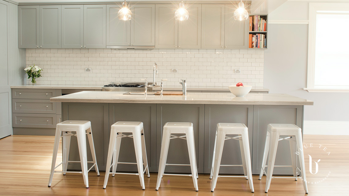 Hamptons Kitchen style with soft grey shaker cabinetry, marble benchtop, subway tiles and an island with white seating, in Kensington, Sydney.