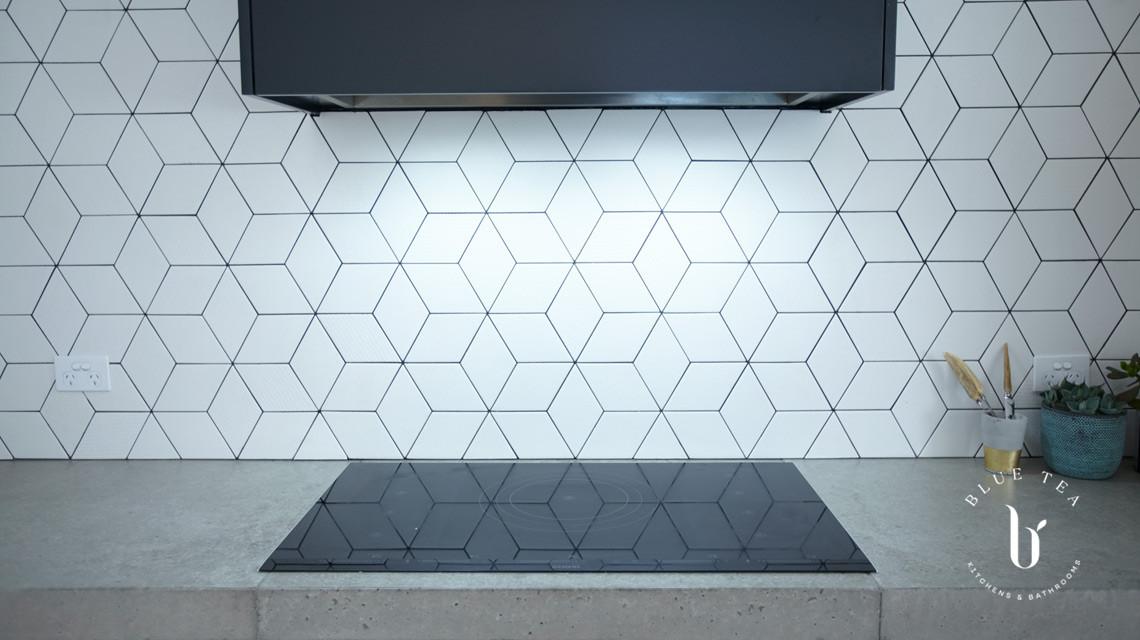 Geometric tiled, kitchen splashback with black cooktop and rangehood, Waterloo, Sydney.