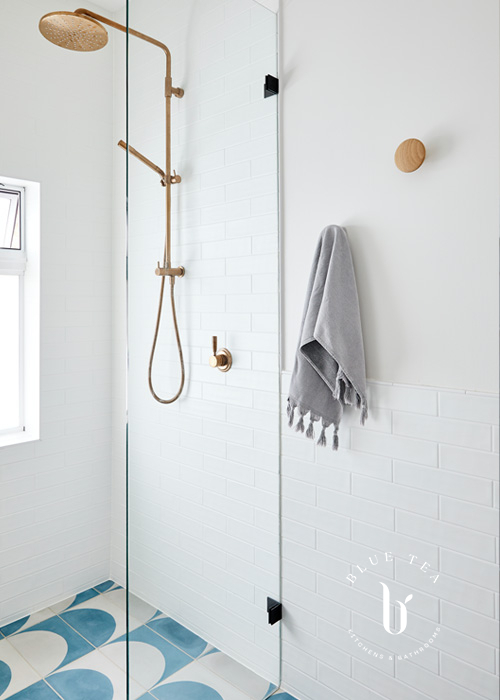 Summer Hill Bathroom Design geometric tiles and a brass shower head.