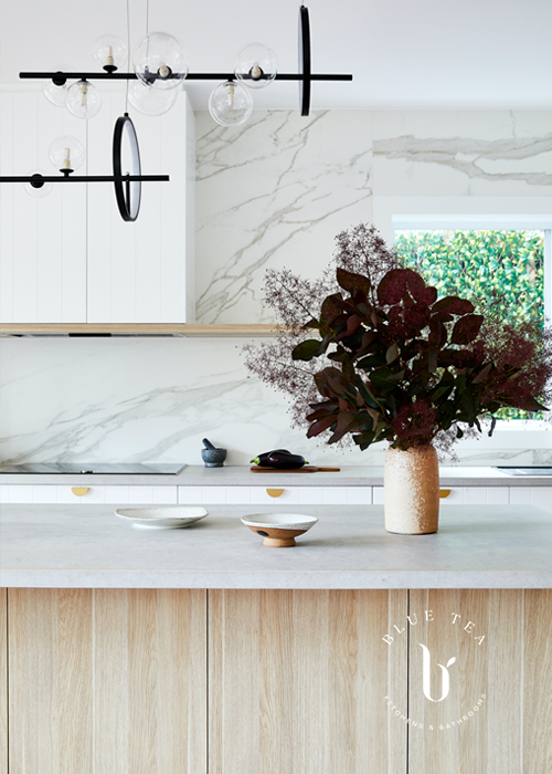 oak laminex kitchen island with a concrete benchtop by Caesarstone, feature lighting and a marble feature splashback.