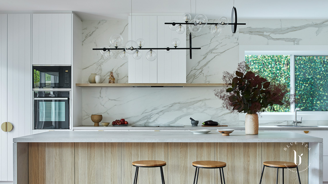 A white kitchen in Bondi: v-groove panels, oak timber and brass detailing, a concrete Caesarstone benchtop and marble feature splashback.