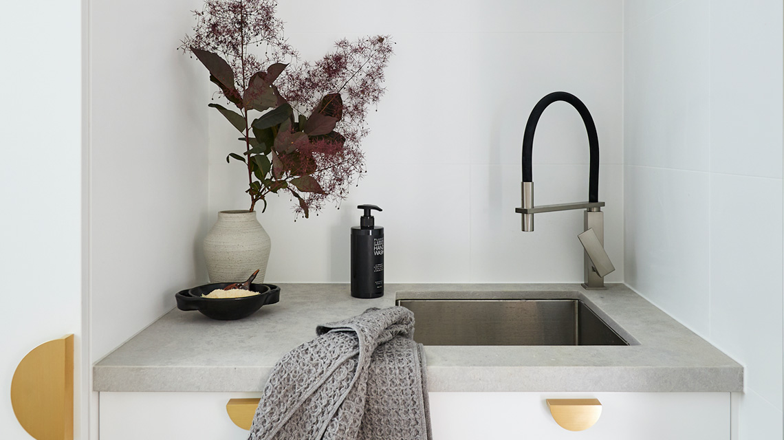 small laundry design in Bondi showcasing a concrete benchtop, undermount laundry sink and brass handles.