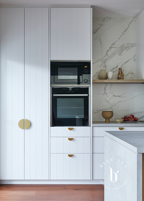 White v-groove kitchen doors, a concrete bencthop by Caesarstone, and brass feature cabinet handles, with an open timber shelf and marble splashback.