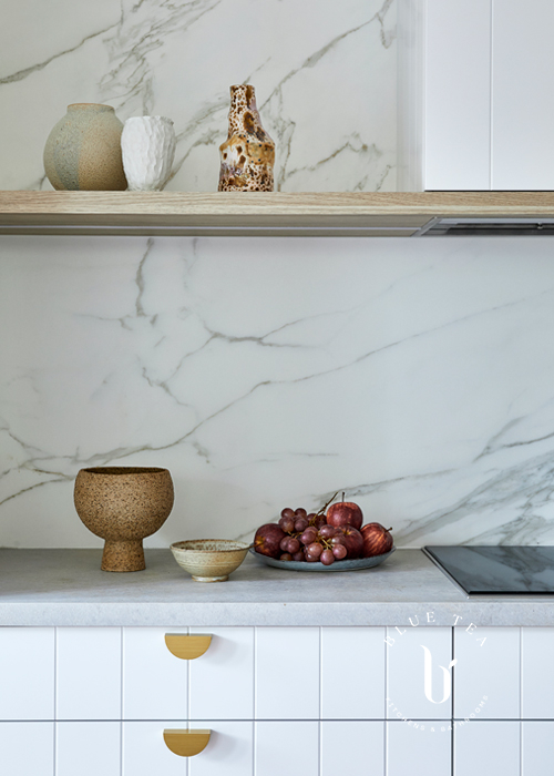 Open oak timber shelf with a marble splashback and v-groove drawers with brass accents. Kitchen in Bondi.