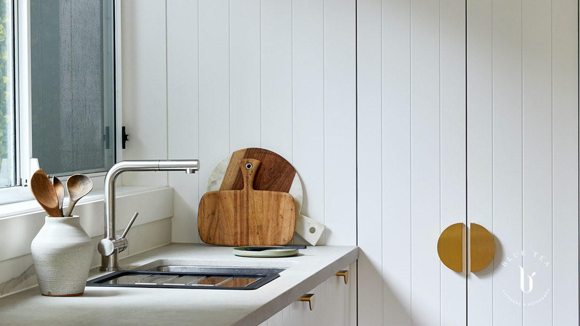 White v-groove kitchen doors, a concrete bencthop by Caesarstone, and brass feature cabinet handles. Kitchen in Bondi.