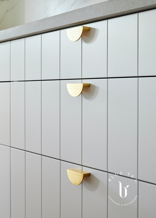 Brass half-moon cabinetry handles by Lo and Co, with v-groove kitchen drawers and a concrete benchtop. Kitchen in Bondi.