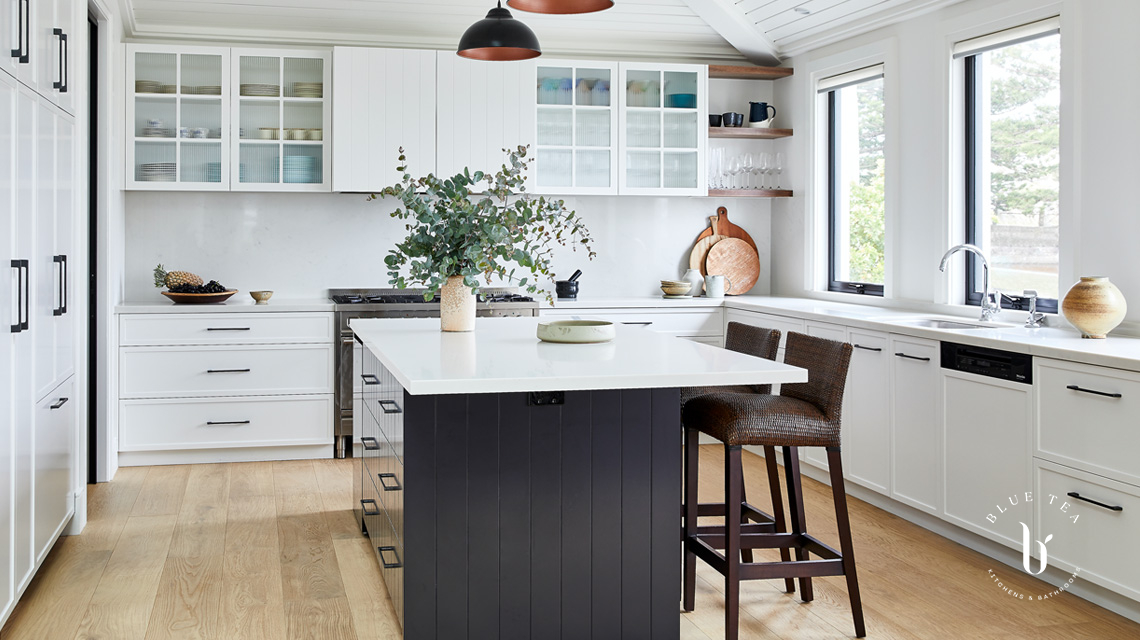 Clovelly kitchen with white shaker doors, glass fluted cabinetry, a dark kitchen island and feature lighting