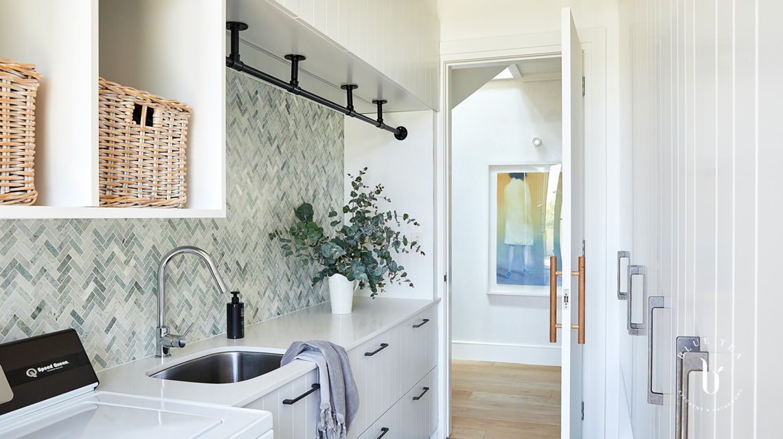 White v-groove laundry doors and a green marble splashback in Clovelly