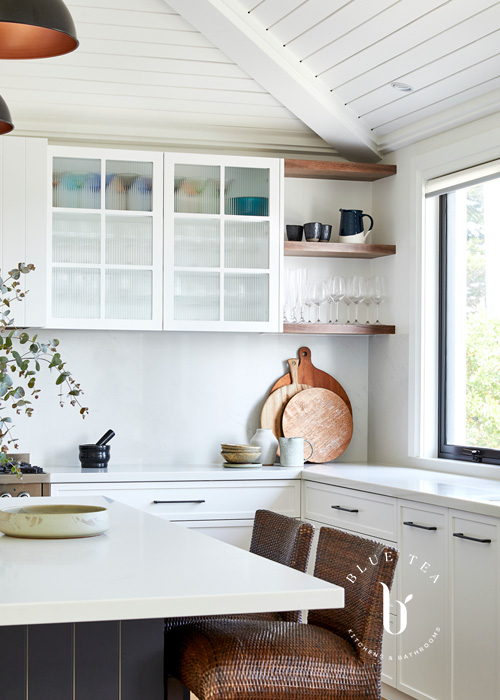 Glass fluted doors, open timber shelves, a dark kitchen islans and a carrara splashback and benchtop in Clovelly