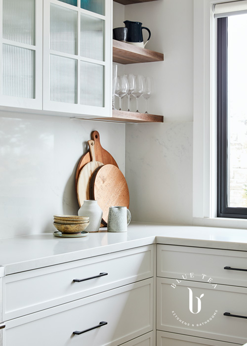 Corner detail showcasing Glass fluted doors, open timber shelves and a carrara splashback and benchtop in Clovelly