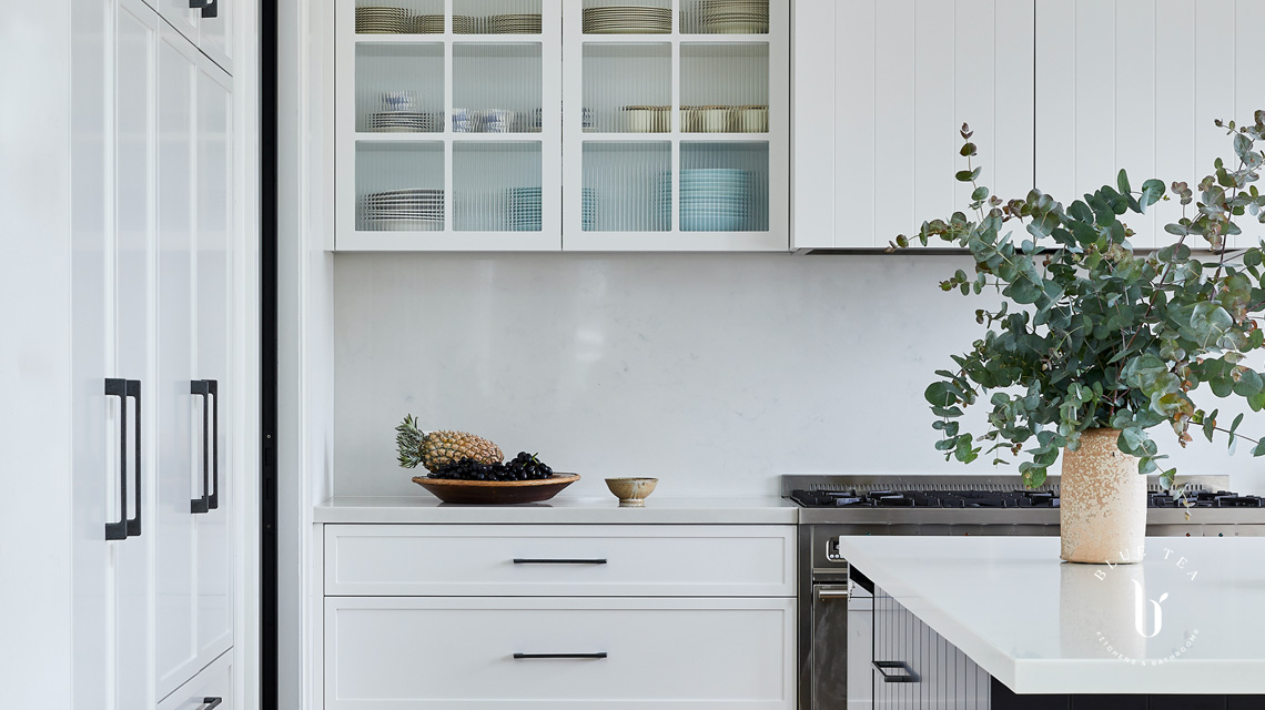 White slimline shaker cabinetry and a dark kitchen island with carrara marble benchtop and splashback in Clovelly