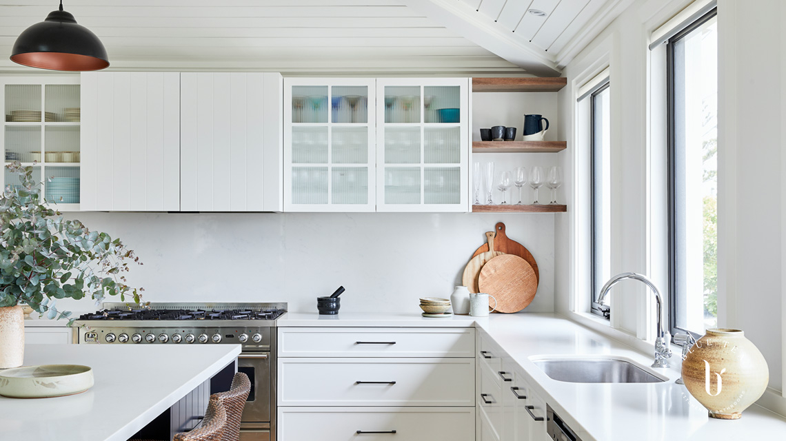 Glass fluted doors and open timber shelves in a white kitchen, Clovelly.