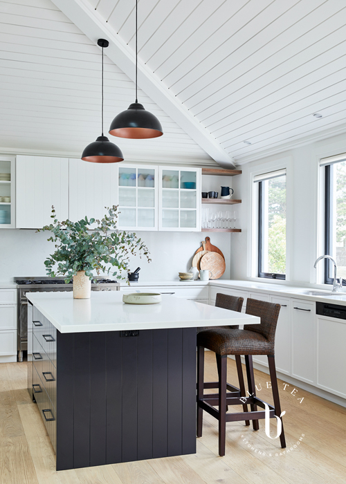 Clovelly kitchen with white shaker doors, glass fluted cabinetry, a dark kitchen island, feature lighting and a pitched ceiling