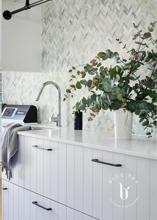 White v-groove laundry doors and a green marble herringbone splashback in Clovelly